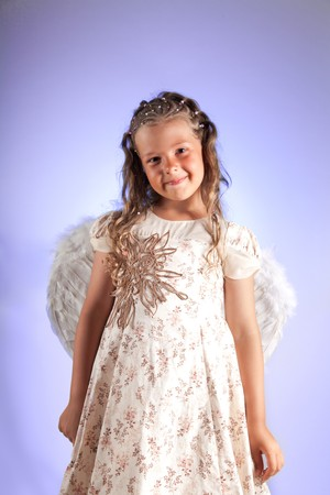 Cute little girl with pigtail hairstyle and angel wings, studio shot on purple background  photo