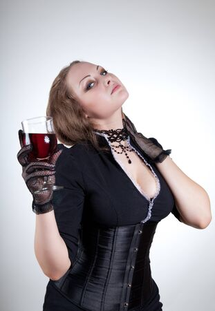 Sexy young woman with glass of red wine, studio shot  photo