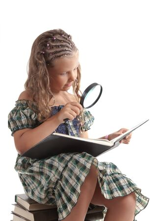Little girl holding magnifying glass, isolated on white background   photo