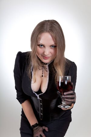 Sexy woman with glass of red wine, studio shot  photo