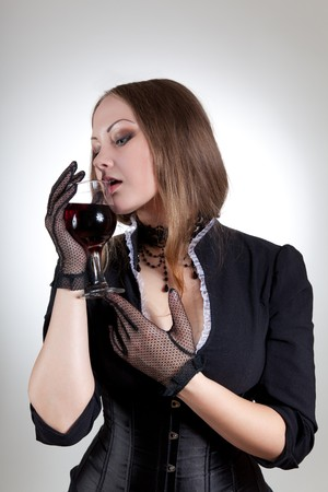 Sensual woman with glass of red wine, studio shot  photo