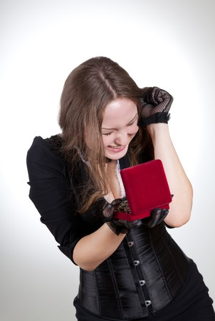 Emotional young woman with gift box full of jewelry, studio shot Stock Photo - 7723523