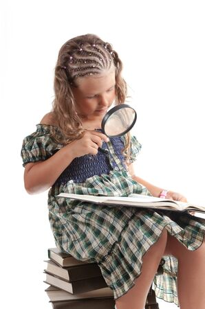 Cute girl holding magnifying glass, isolated on white background   photo