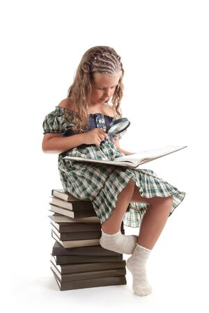 Little girl with magnifying glass reading book, isolated on white background  photo