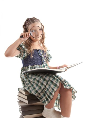 Funny shot of little girl looking through magnifying glass, isolated on white background  photo