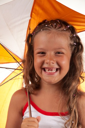 suntanned: Little girl holding umbrella and showing two missing teeth, studio shot