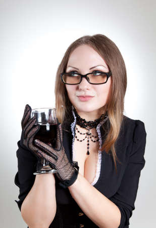 Romantic woman wearing glasses and holding wine glass, studio shot  Stock Photo - 7725696