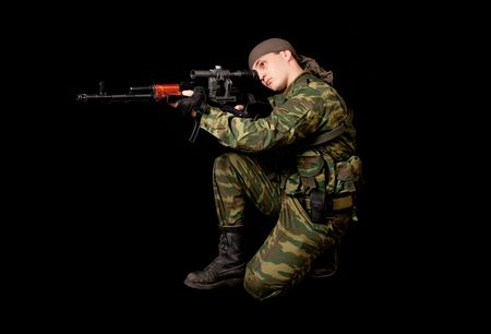 Soldier in uniform with rifle, isolated on black background  photo