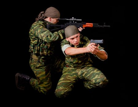 Two soldiers in camouflage uniform with weapon, isolated on black background  photo