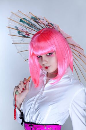 Young woman with oriental make-up holding Japanese umbrella   photo