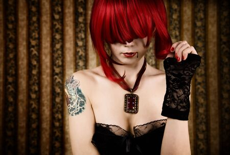 Redhead vampire with drop of blood, glamour background   photo