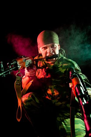 Aggressive soldier with weapon, focus on face   photo
