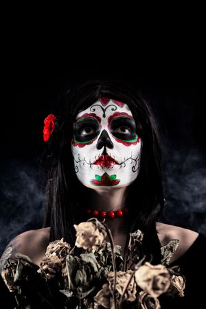 mystical woman: Sugar skull girl with dead roses, studio shot over black smoky background  Stock Photo