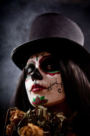 skull character: Sugar skull girl in tophat holding dead roses, studio shot  Stock Photo