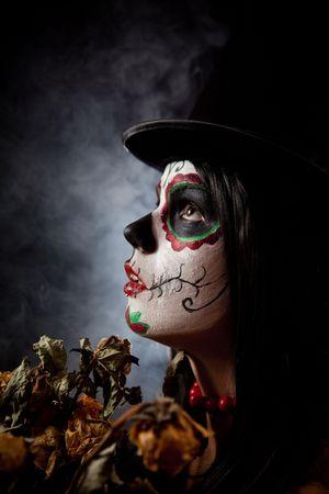 sugar skull: Sugar skull woman in tophat, holding dead roses, studio shot