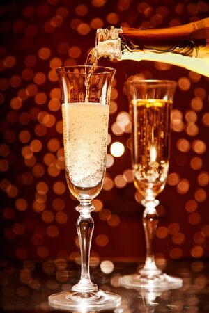 Champagne pouring into elegant glass over holiday bokeh background