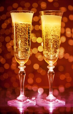 Two champagne glasses over holiday bokeh background  photo