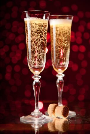 Two crystal champagne glasses over holiday bokeh background
