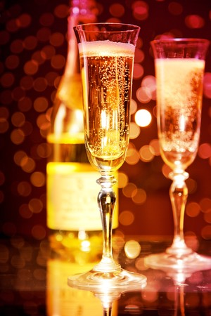 Champagne glasses and bottle over holiday bokeh background, focus on first glass