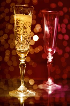 Two champagne glasses over colorful holiday bokeh background  photo