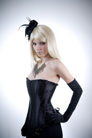 Young woman in black corset, studio shot on white background  photo