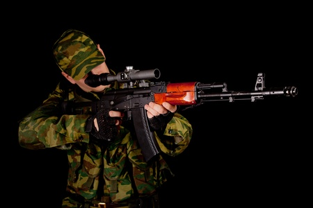 commando: Soldier in uniform with rifle, isolated on black background