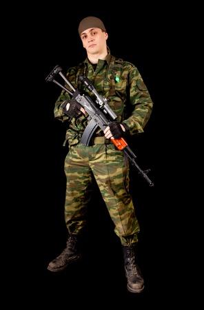 Soldado en uniforme con arma, aislado en fondo negro