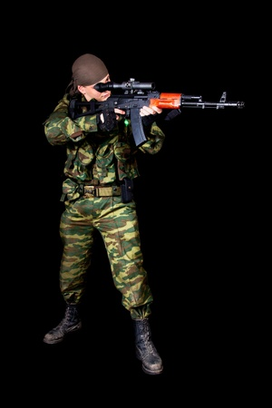 Full length shot of soldier with weapon, isolated on black background  photo