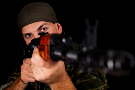 weaponry: Soldier in uniform with rifle, selective focus on face