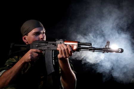 violence and trigger: Soldier with rifle, focus on weapon, smoke on background