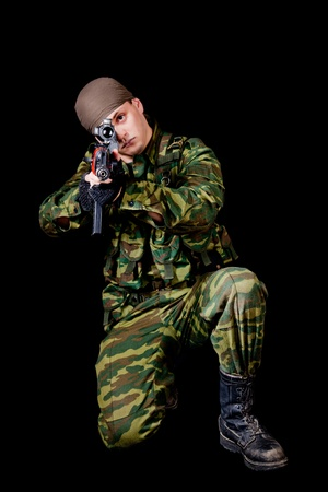 Soldier with weapon, isolated on black background  photo