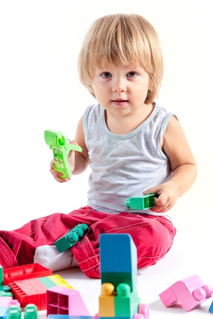 Cute little boy playing with blocks, isolated on white background  photo