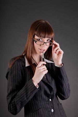 Thoughtful business woman wearing glasses, studio shot  photo