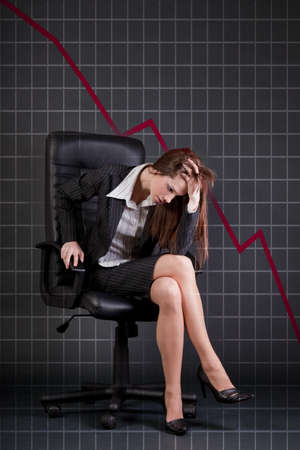 worried executive: Depressed businesswoman sitting in office armchair, chart on background  Stock Photo