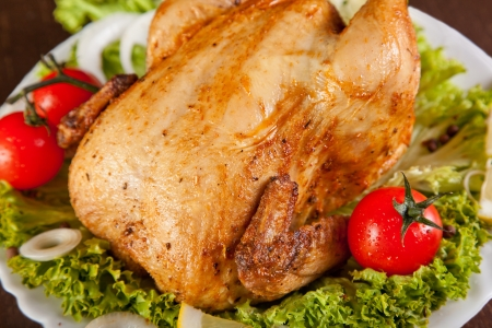 Close-up of roast chicken with fresh vegetables, studio shot  photo
