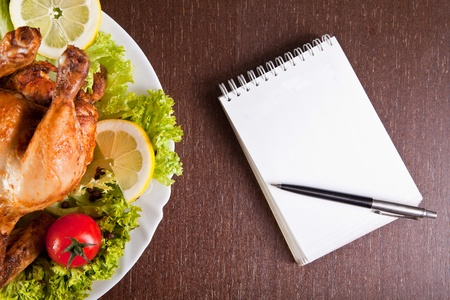 Restaurant table with roast chicken, notebook and pen, ready for order Stock Photo - 9627101