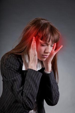 dolor de cabeza: Mujer de negocios con dolor de cabeza, studio disparo  Foto de archivo