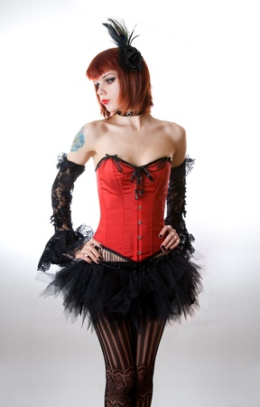 Attractive woman in red corset and black skirt, studio shot over white background  photo