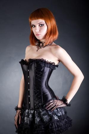 Attractive woman in black corset and layered skirt, studio shot  photo
