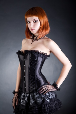 Attractive woman in black corset and layered skirt, studio shot  photo