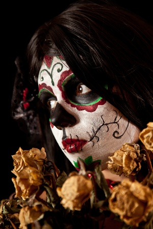 Portrait of Sugar skull girl with dead roses, isolated on black background