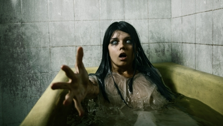 mystique: Scary girl in bath stretching her hand to camera, Halloween theme  Stock Photo