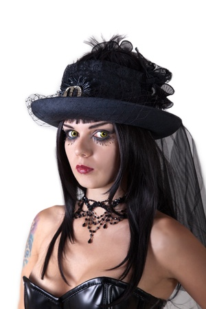 Young witch with scary yellow eyes, wearing Halloween veil hat, isolated on white background  photo
