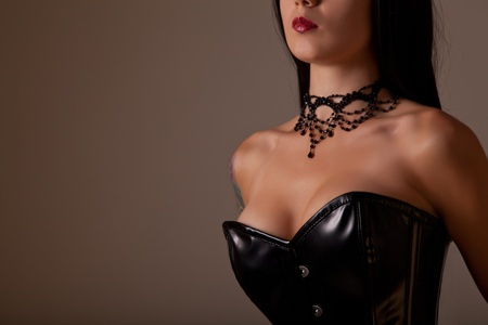 Close-up shot of busty woman in black corset, studio shot on creamy background  Stock Photo - 10842686