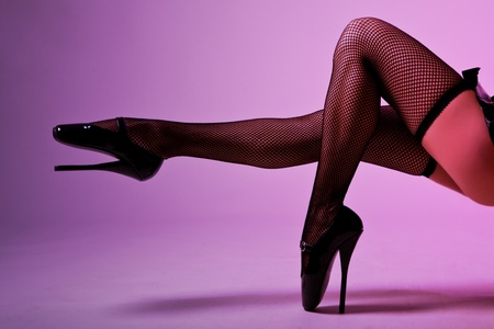Sexy female legs in fishnet stockings and extreme fetish ballet shoes, studio shot  Stock Photo - 10842685