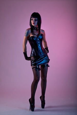 Fetish woman wearing leather corset and extreme ballet shoes, studio shot