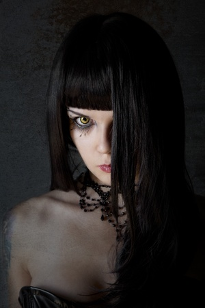 Young witch with yellow eyes and black long hair, textured background  photo