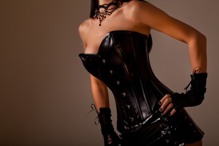 Close-up shot of busty woman in black leather corset, studio shot on golden background Stock Photo - 10901100