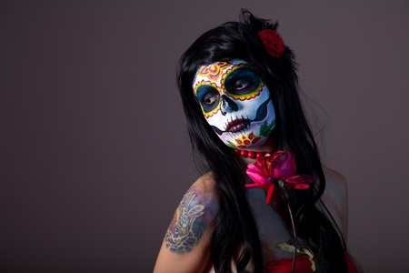 Sugar skull girl with red rose, professional body-art  photo
