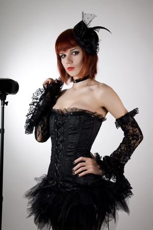 Attractive woman in black corset, gloves and tutu skirt, studio shot  photo